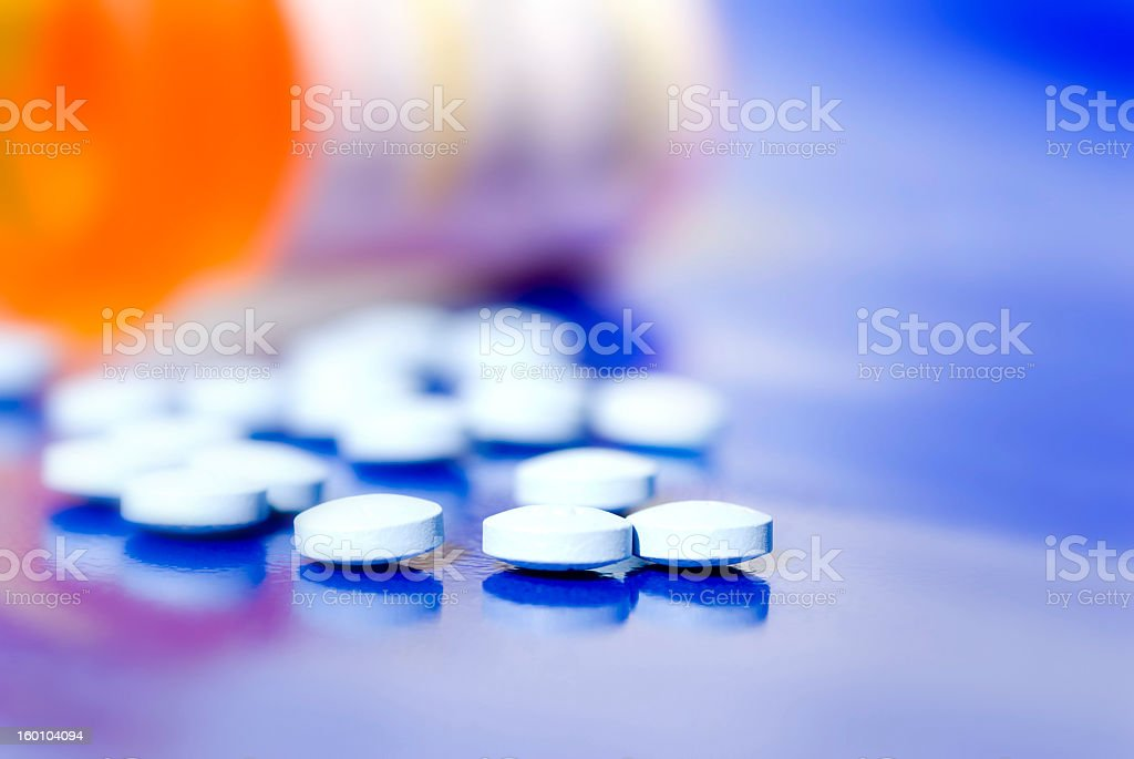 A bottle of pills on the side and pills that fell out stock photo