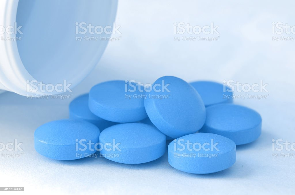 Bottle of pour out blue pills of drugs stock photo