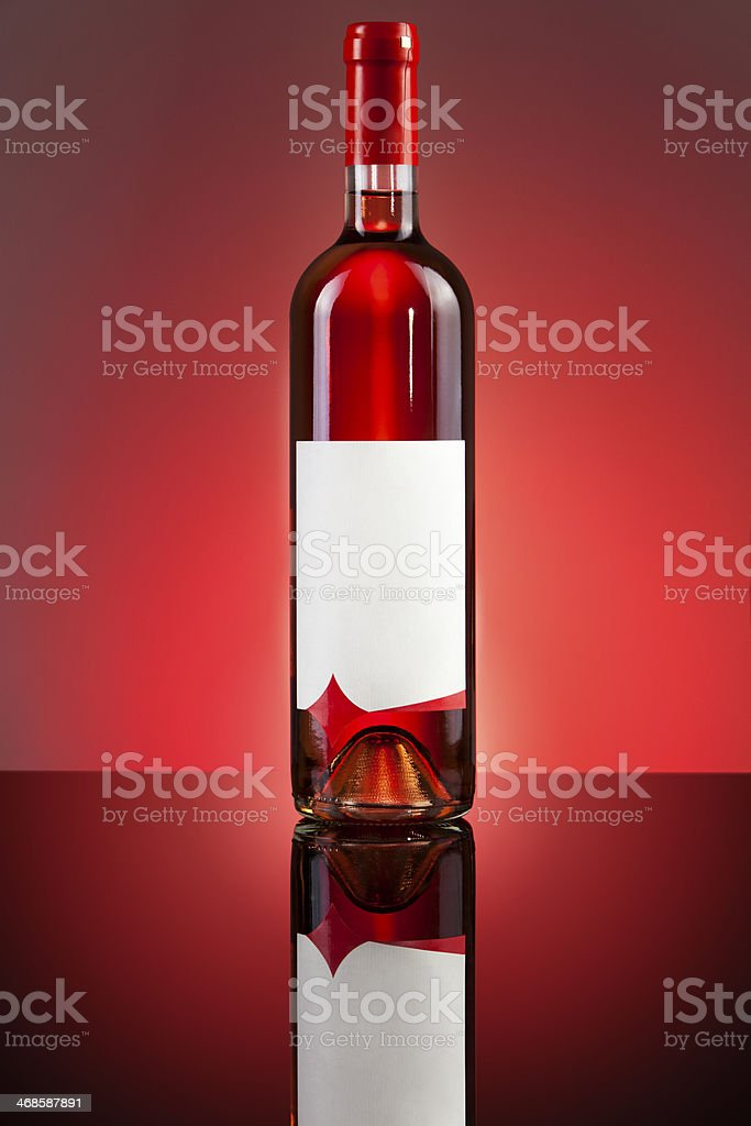 bottle of red vine reflecting on a glass surface royalty-free stock photo