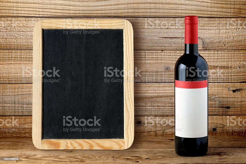 Bottle of red wine and blank blackboard stock photo