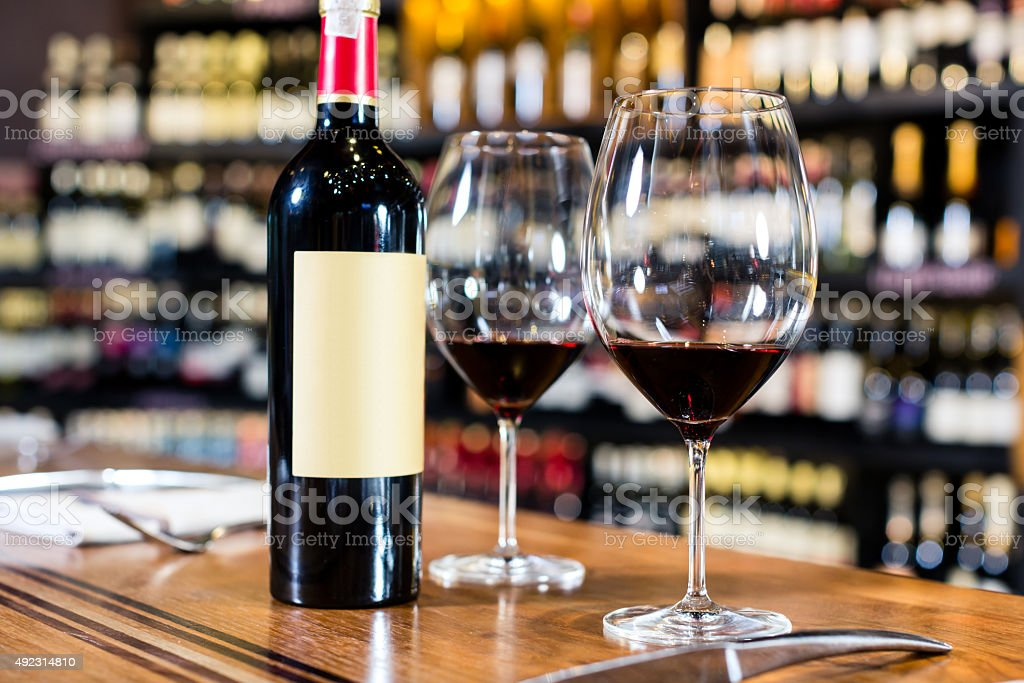 Bottle of red wine and two glasses in wine shop stock photo
