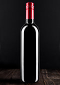 Bottle of red wine dark glass on wooden background