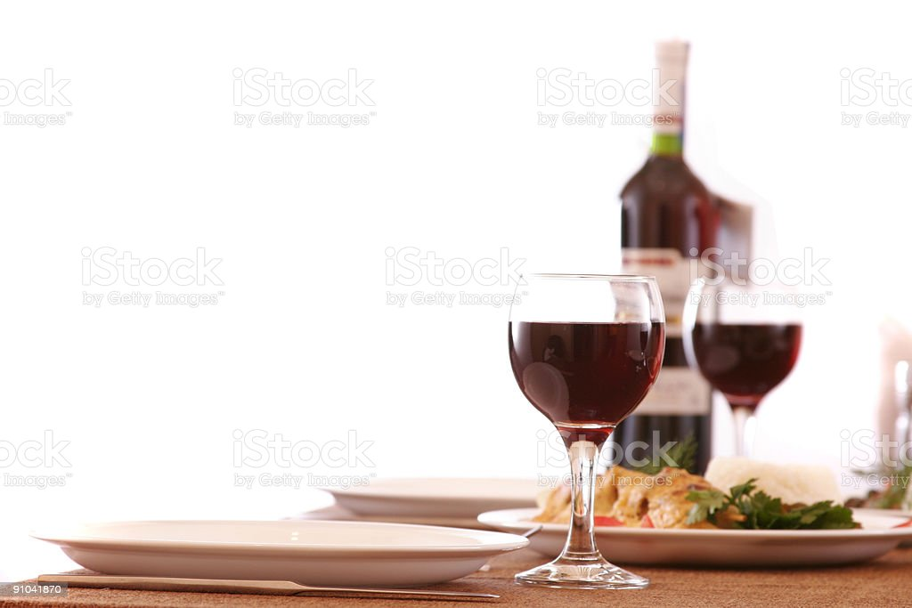 A bottle of red wine into wine glasses at the dinner table royalty-free stock photo