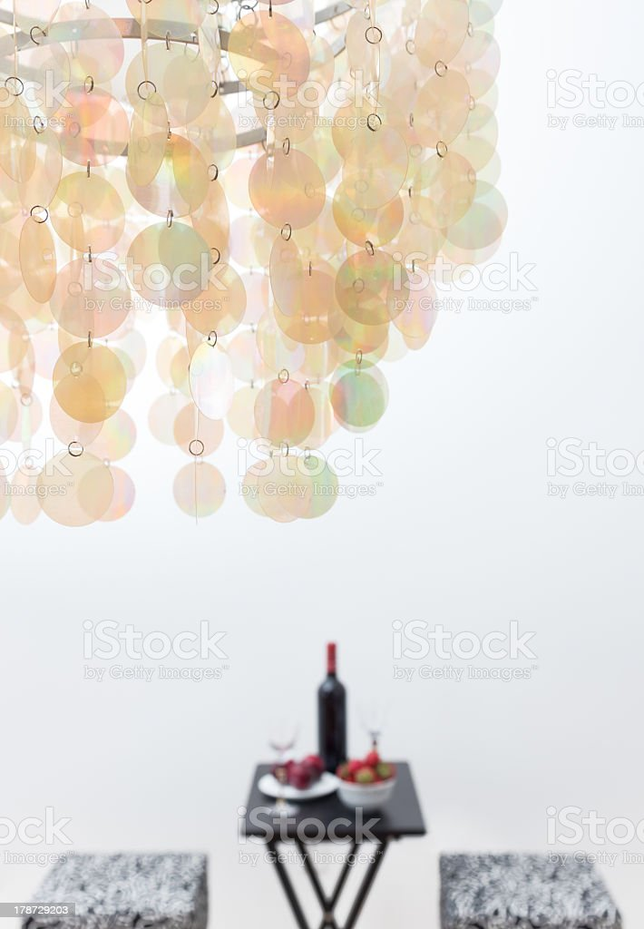 Bottle of red wine on a table, and beautiful chandelier royalty-free stock photo