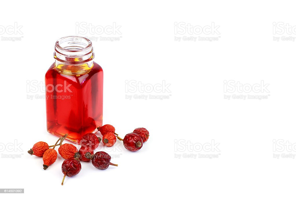 Bottle of rose hip oil on white background stock photo