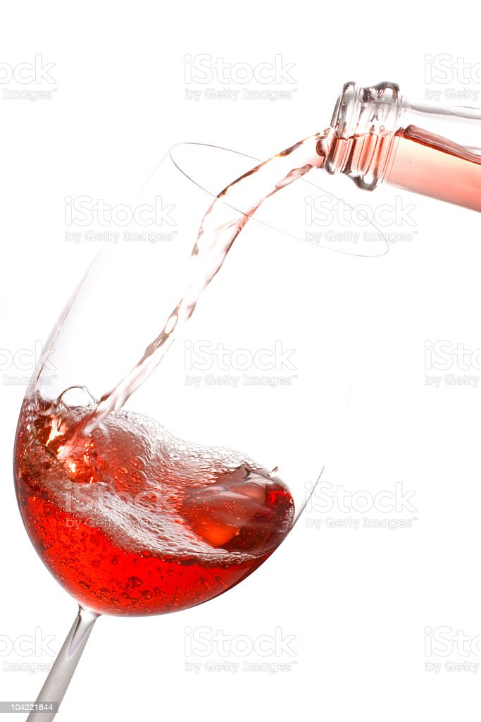 Bottle of Rose Wine Pouring into a Glass over White. stock photo