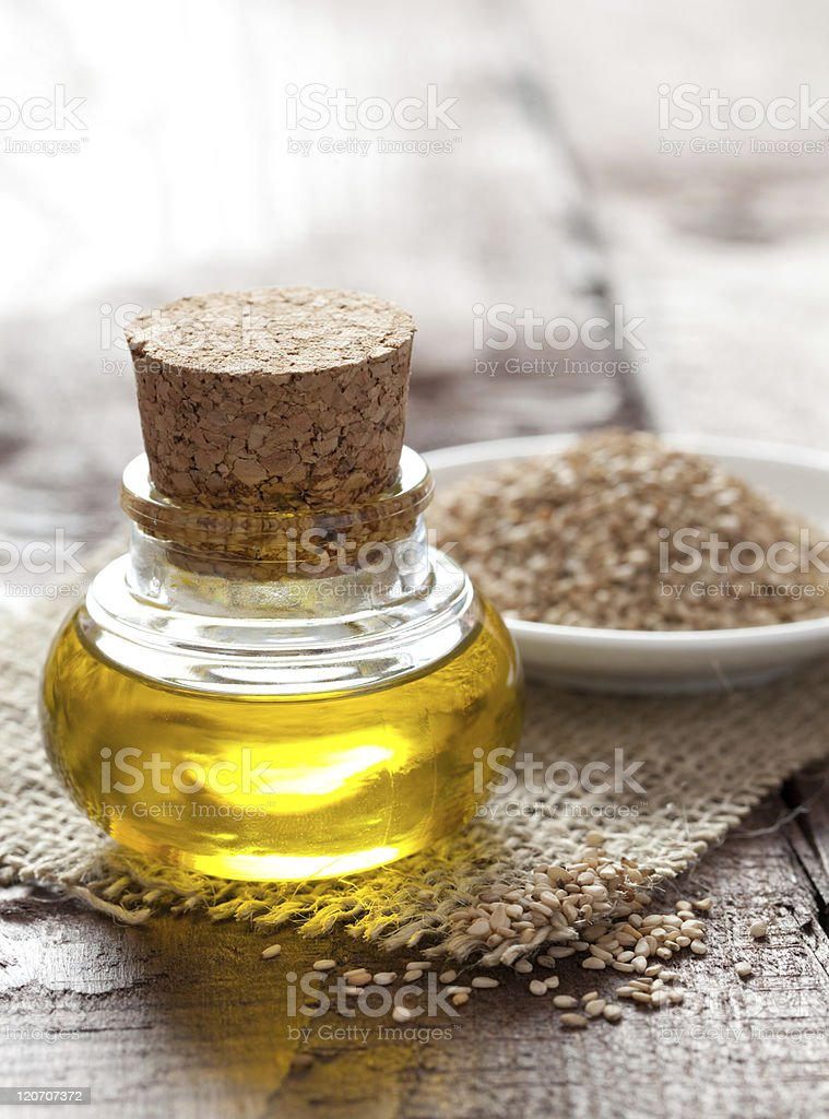 Bottle of sesame oil and sesame seeds stock photo