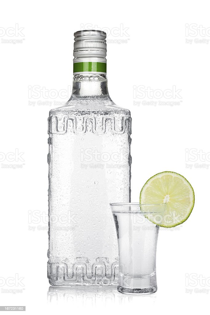 Bottle of silver tequila and shot with lime slice royalty-free stock photo