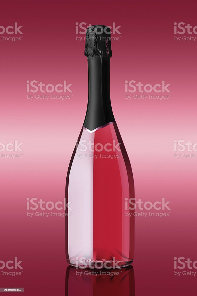 bottle of sparkling wine on pink background stock photo