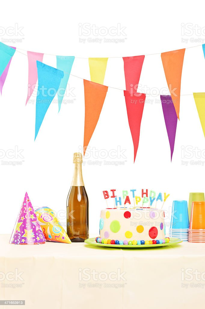 Bottle of sparkling wine, plastic glasses, party hats and cake royalty-free stock photo