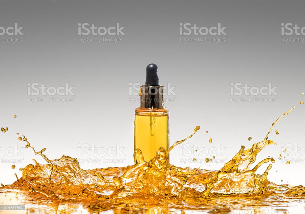 Bottle of the yellow cosmetic oil in the   oil splash stock photo