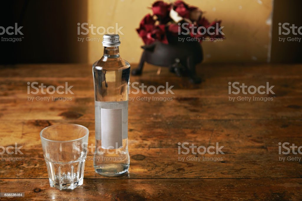Bottle of water and glass in rustic kitchen stock photo
