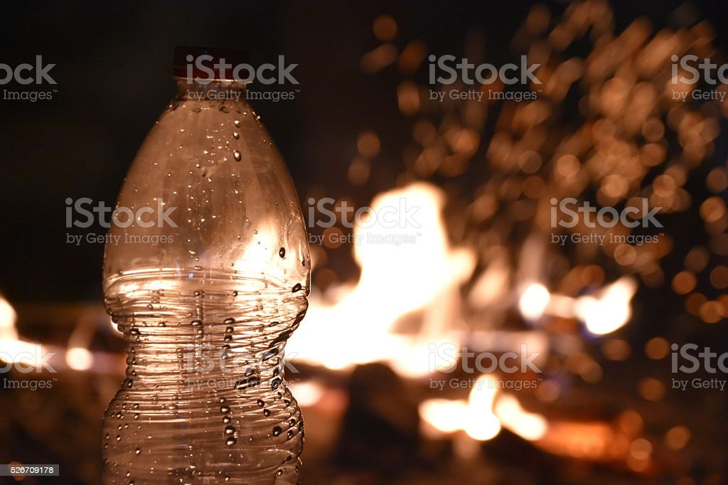 bottle of water on a fire background stock photo
