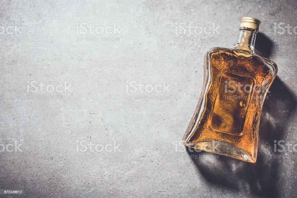 Bottle of whiskey on gray stone table stock photo