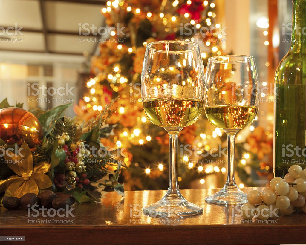 Bottle of Wine and Glasses against Christmas Lights stock photo