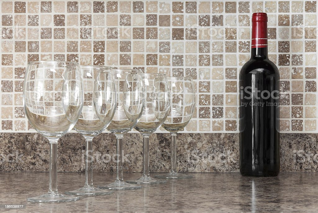 Bottle of wine and glasses on kitchen countertop stock photo
