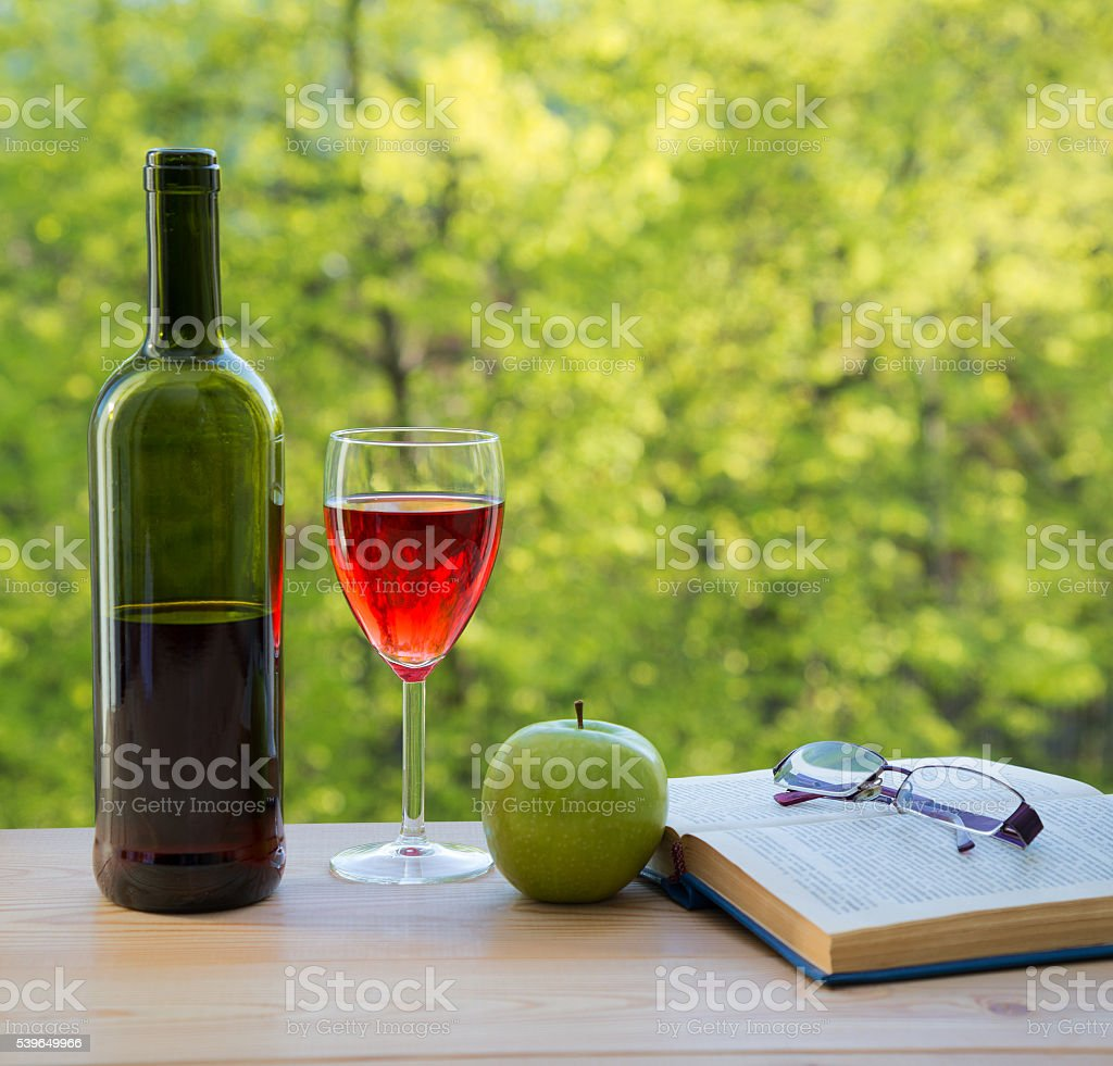 bottle of wine green apple eyeglasses and book on table stock photo