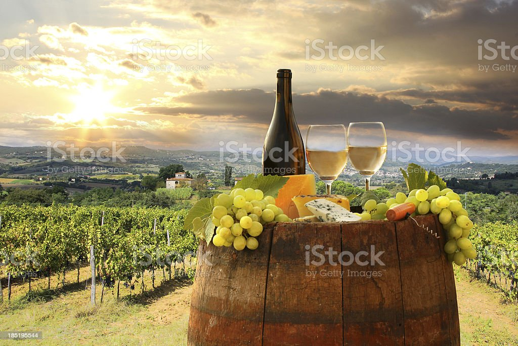 A bottle of wine on a barrel in the land of Italy  stock photo
