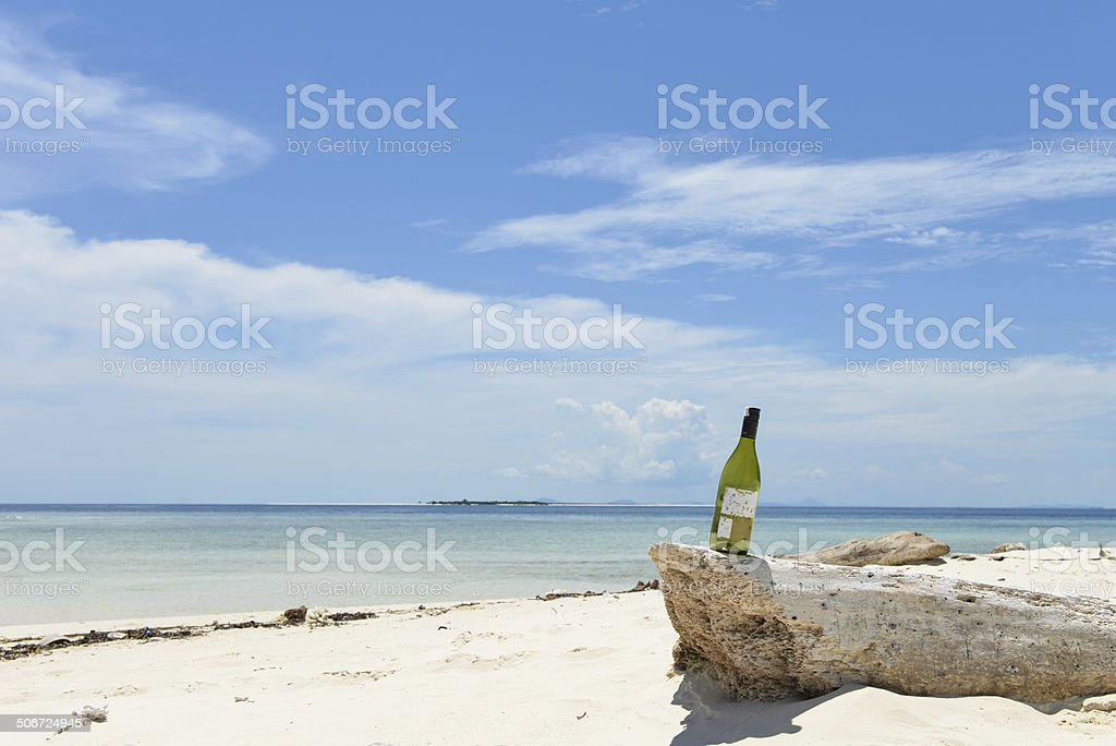 bottle of wine on beach stock photo