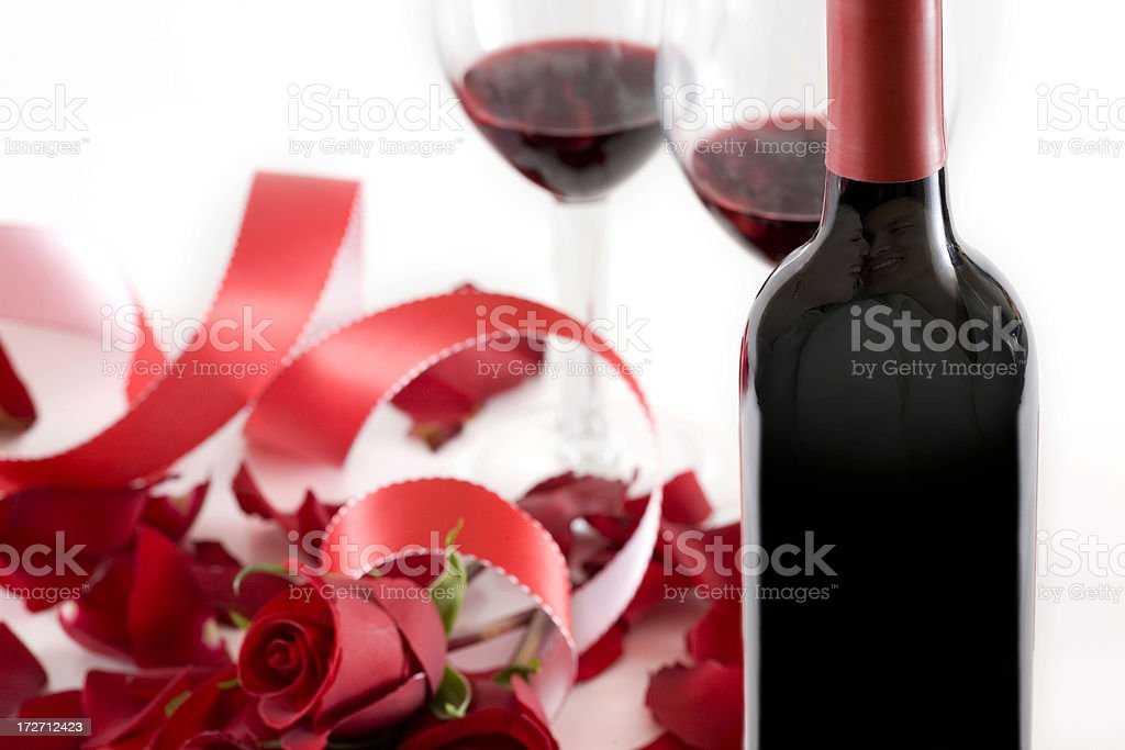 Bottle of Wine Reflecting Young Couple, Roses and Ribbon stock photo