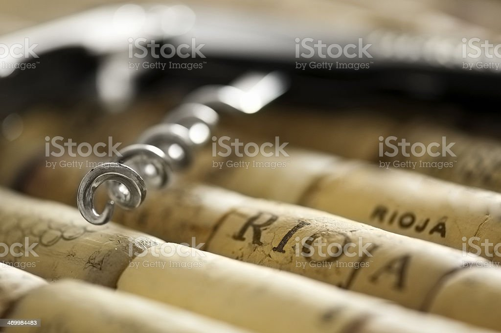 Bottle opening corkscrew lying on a pile of corks stock photo