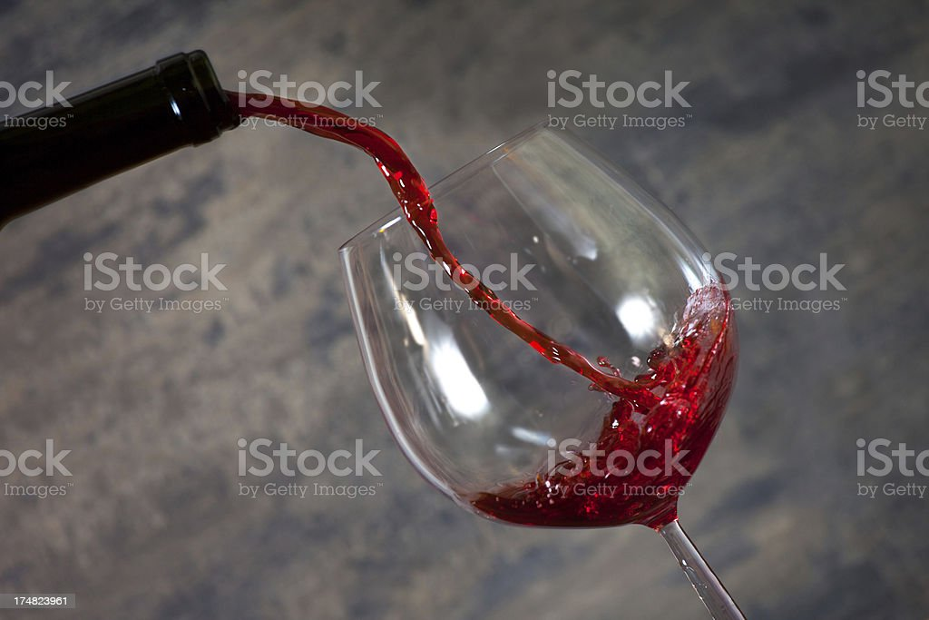 Bottle pouring red wine in a crystal glass royalty-free stock photo
