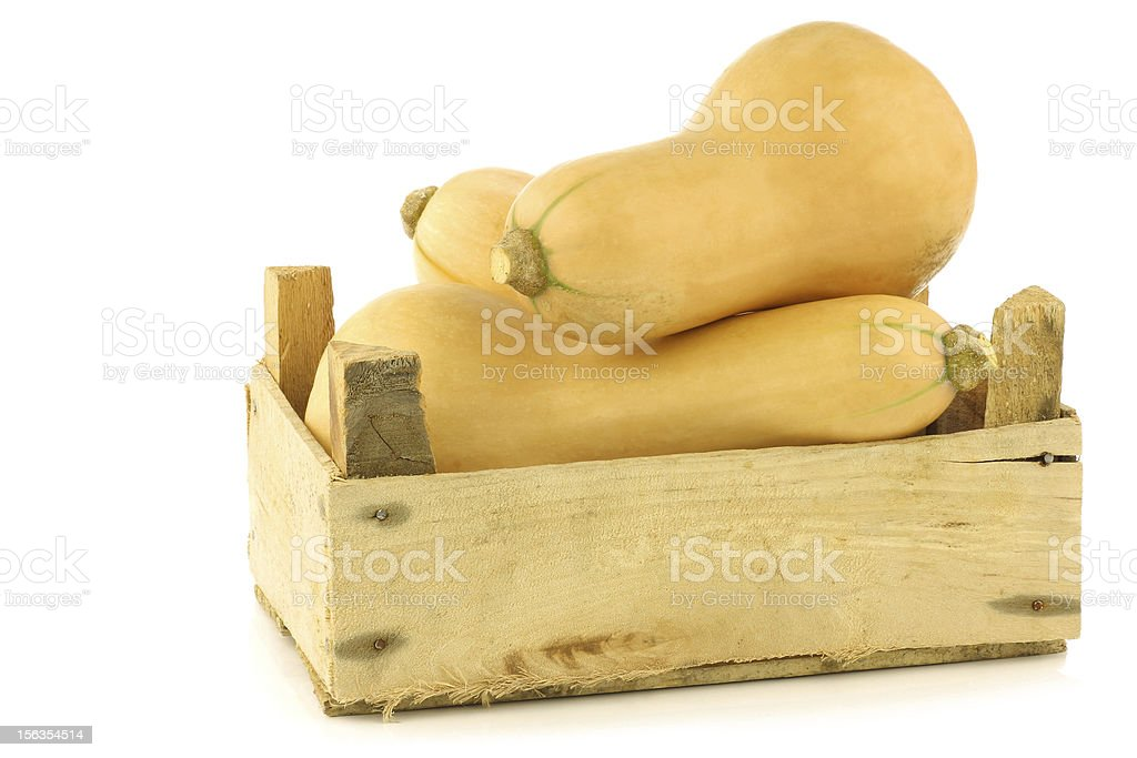 bottle shaped butternut pumpkins in a wooden crate royalty-free stock photo