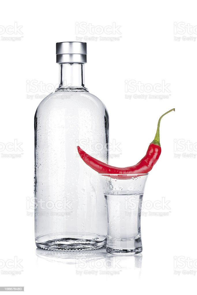 Bottle, shot glass of vodka and red chili pepper stock photo