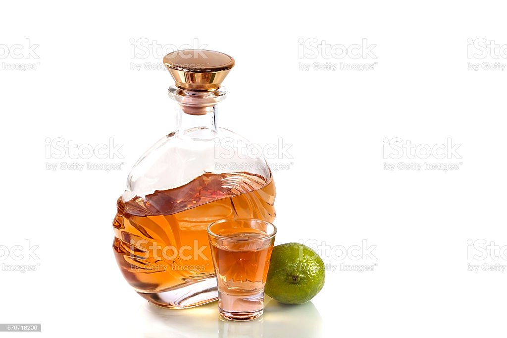 Bottle tequila and shot glass with lime on white background stock photo