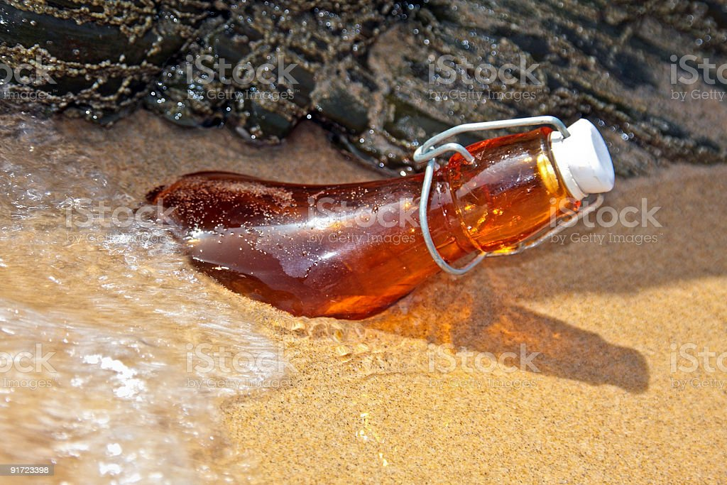 Bottle washed ashore on the beach stock photo
