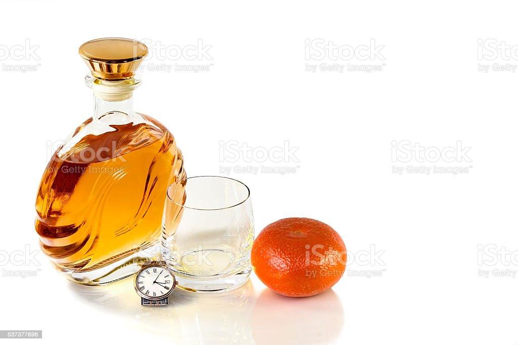 Bottle whiskey and empty tumbler with Mandarin on white background stock photo