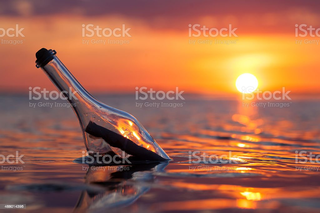 Bottle with a message in the sea stock photo