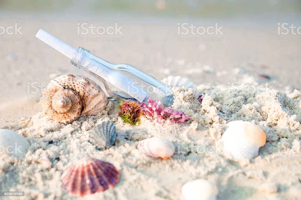 Bottle with a message or letter on the beach. SOS. stock photo