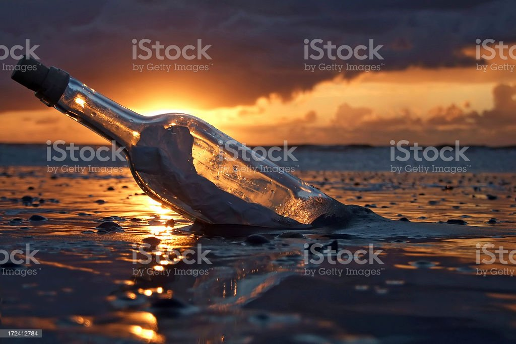A bottle with a message washed up in a beach during sunset stock photo