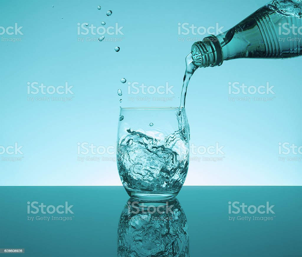 Bottle with creative splashing water in the glass stock photo