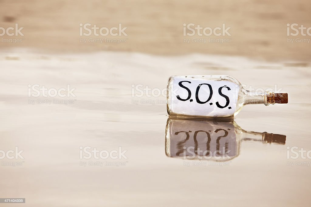 Bottle with desperate SOS message washed up on beach royalty-free stock photo