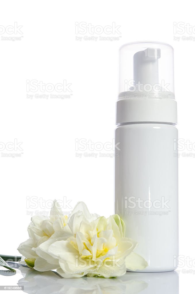 bottle with  lotion and flowers isolated on white stock photo