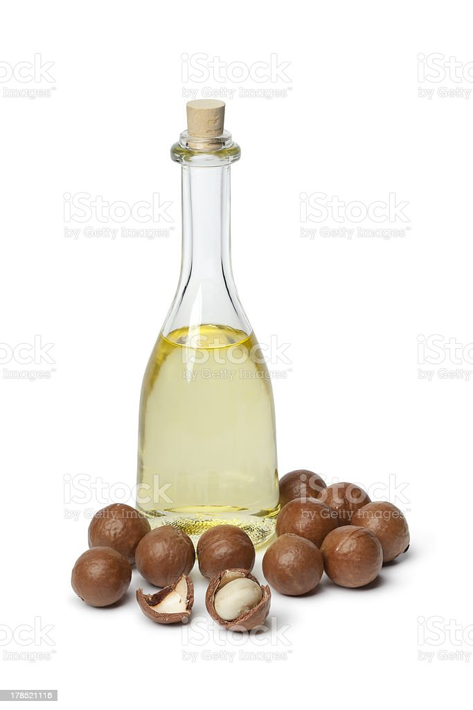 Bottle with Macadamia oil and nuts stock photo