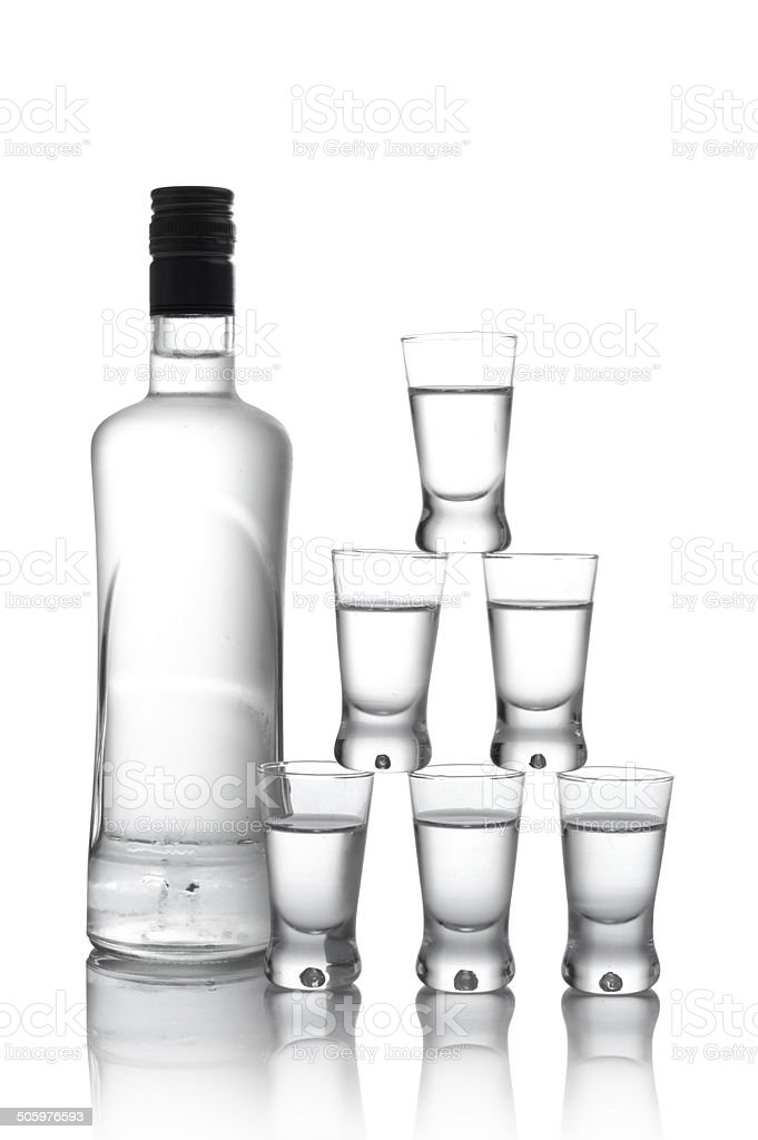 Bottle with many glasses of vodka isolated on white background stock photo