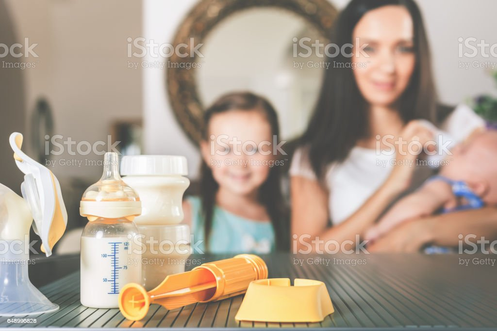 Bottle with milk and manual breast pump stock photo