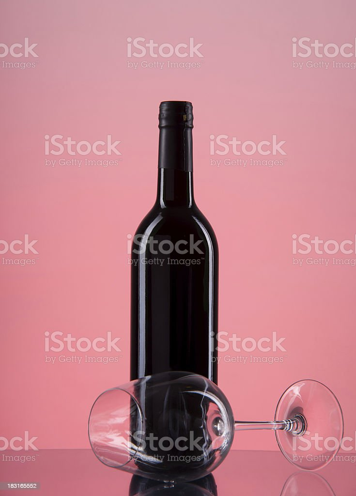 bottle with red wine and glass on a pink gradient royalty-free stock photo