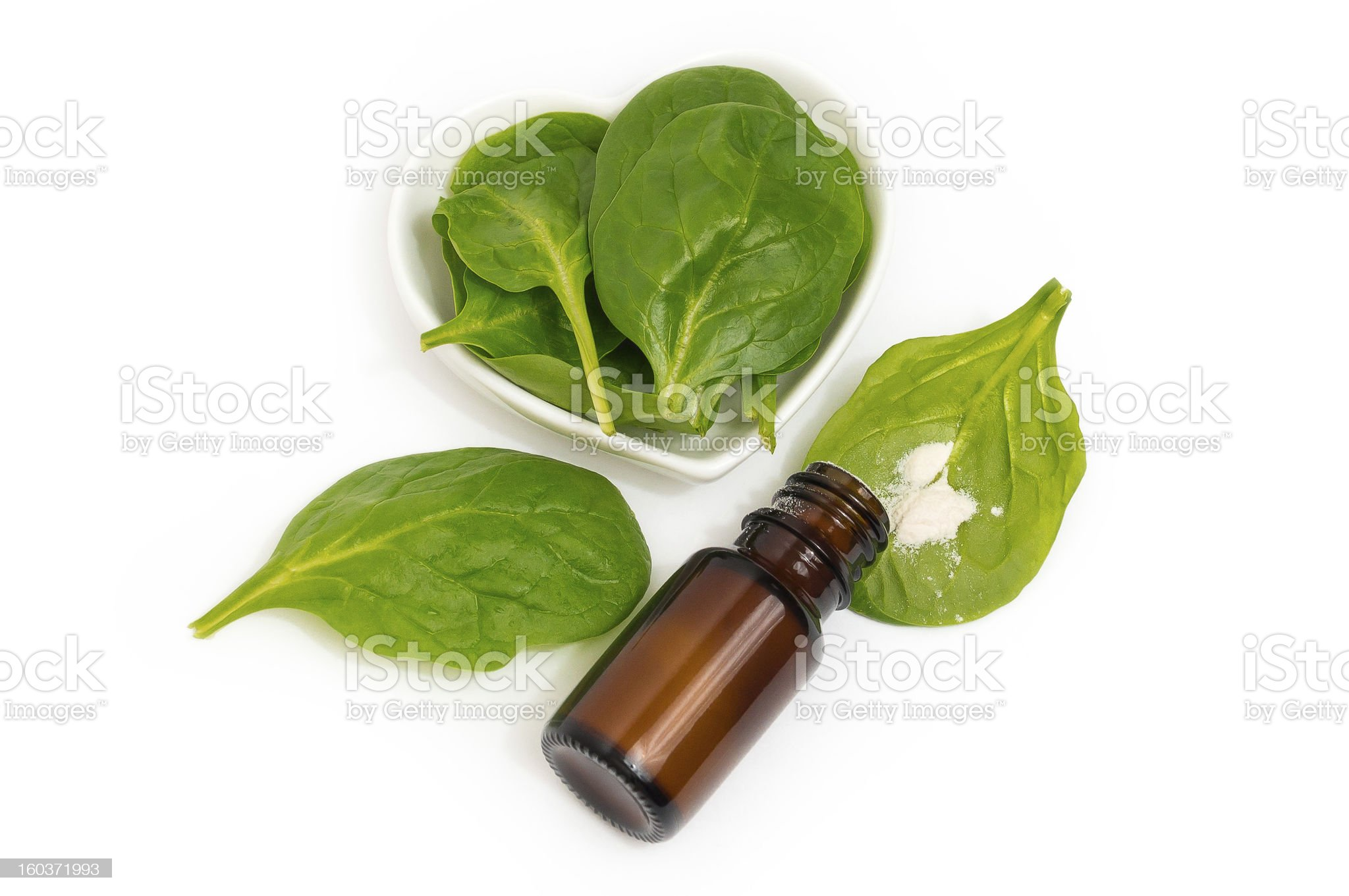 Bottle with White Powder and Spinach on a Heartshaped Plate royalty-free stock photo