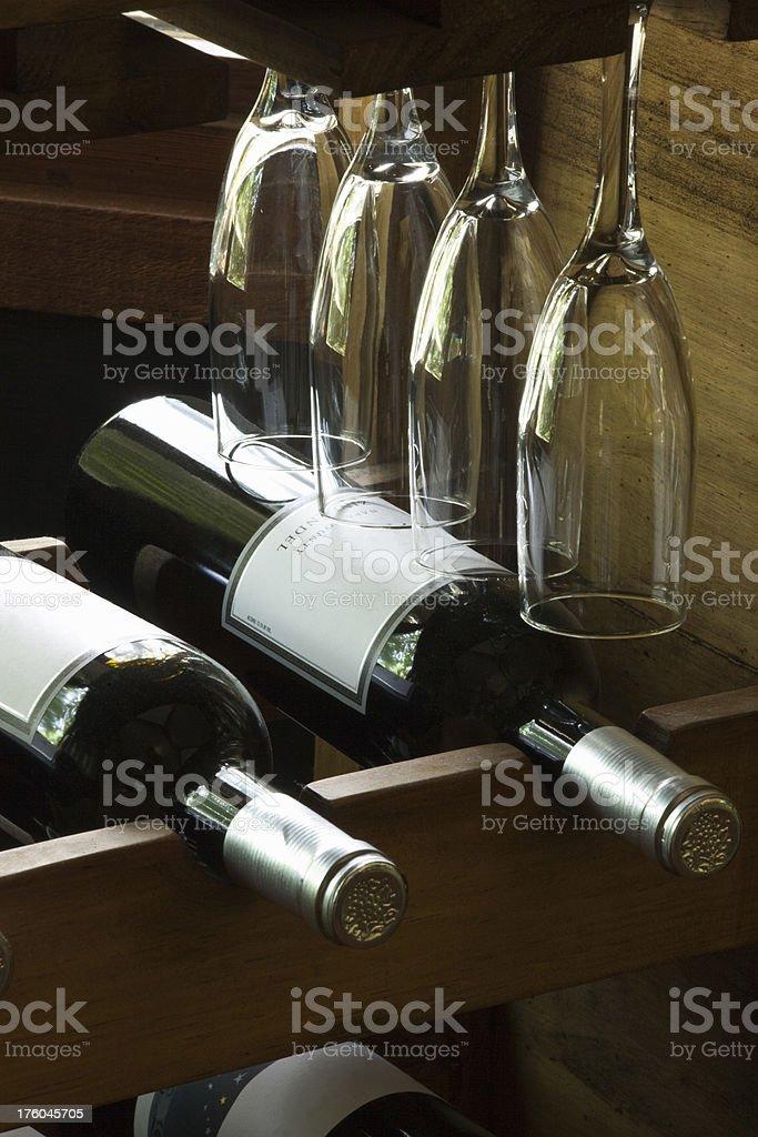 Bottled Wine and Long-stemmed Glasses on Rack royalty-free stock photo