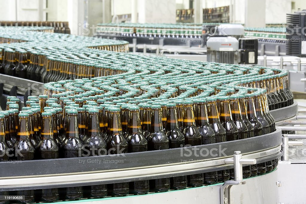Bottles of beer on conveyor in brewery stock photo
