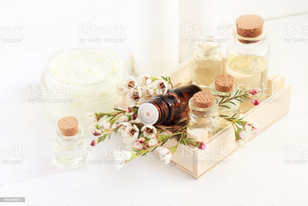 Bottles of essential aroma oil in wooden container with delicate flowers stock photo