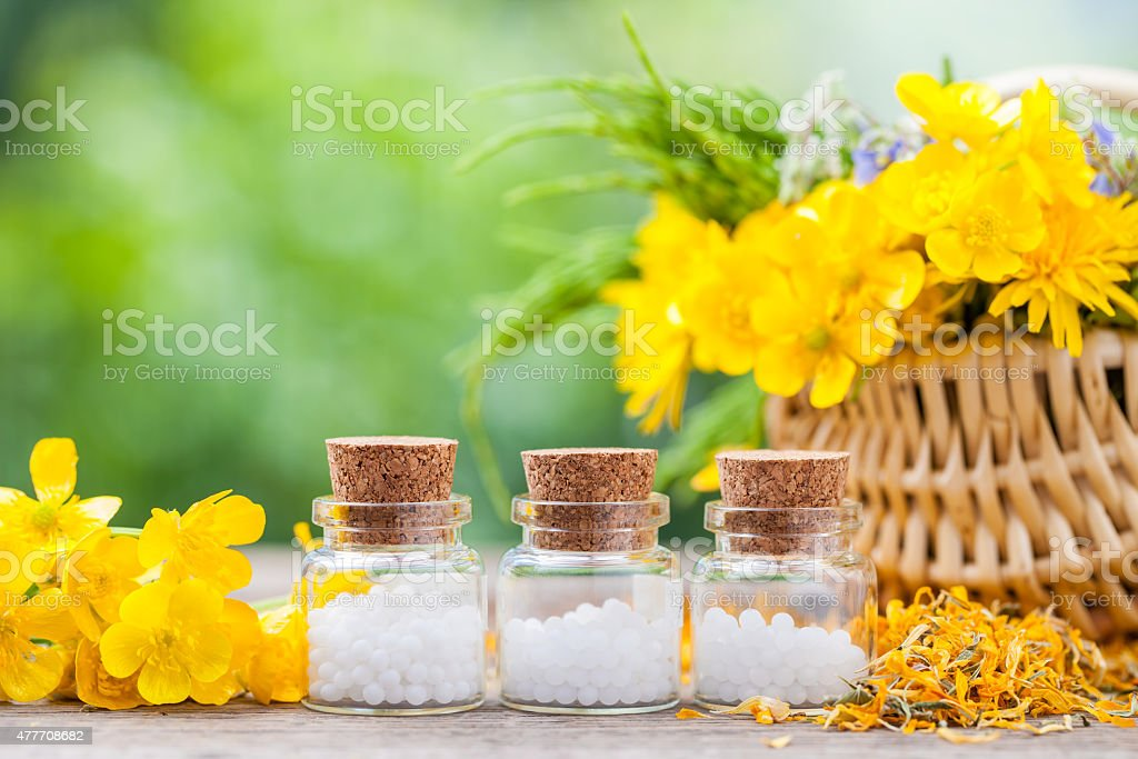 Bottles of homeopathy globules and healthy herbs in  basket stock photo