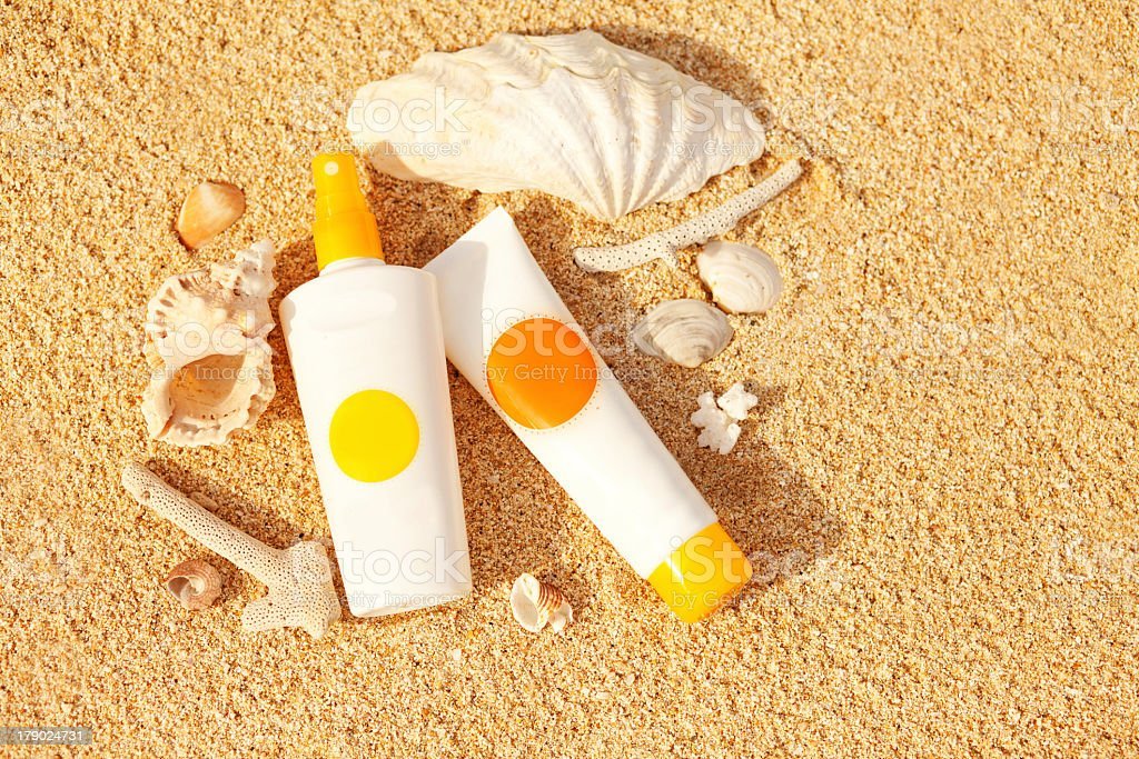2 bottles of sunscreen lotion on the beach next to shells stock photo
