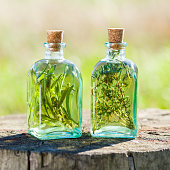 Bottles of thyme and rosemary essential oil or infusion outdoors