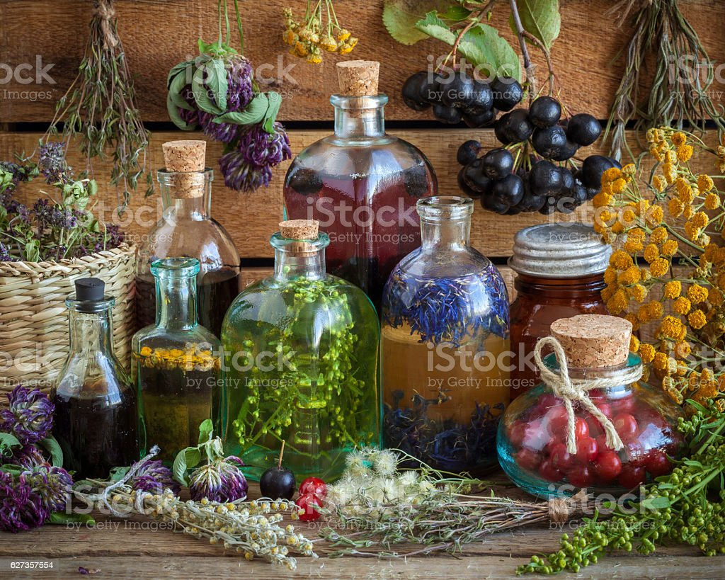 Bottles of tincture, potion, oil, healthy berries and healing herbs. stock photo