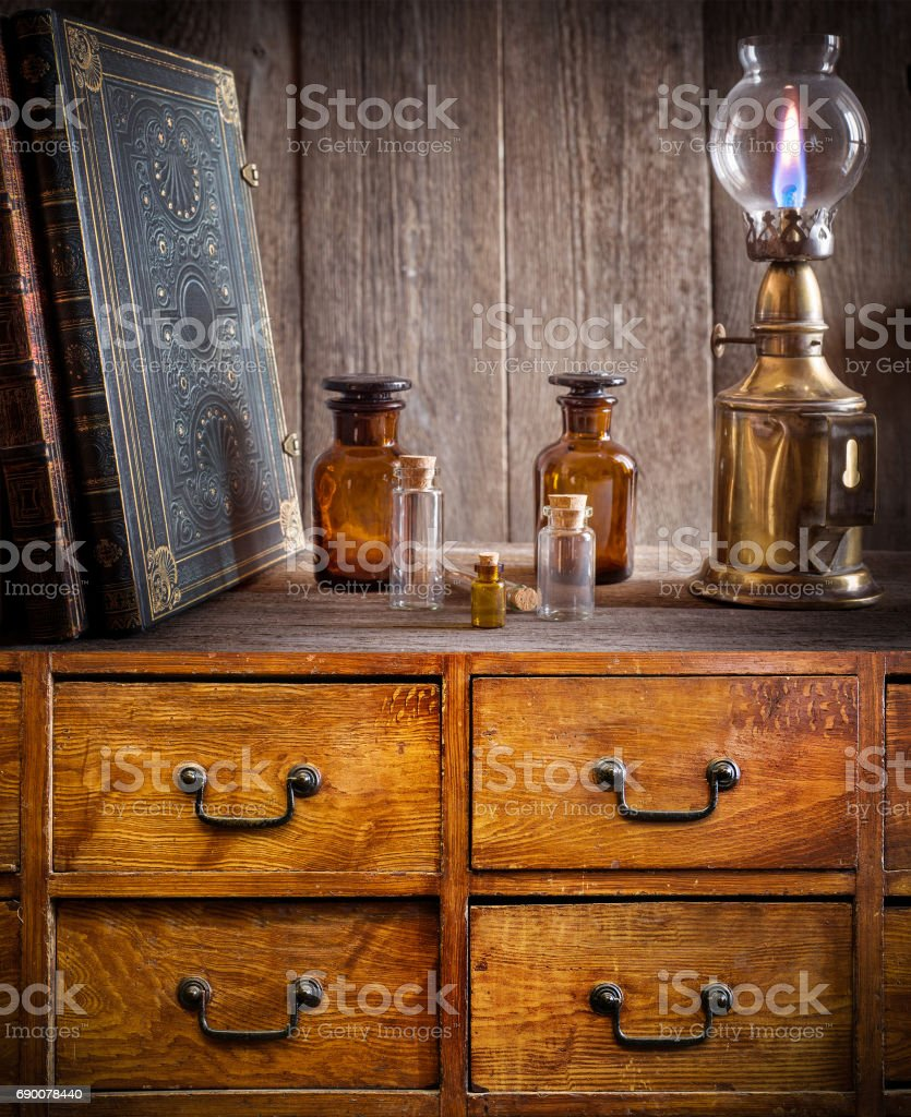 Bottles, old book and lamp on the shelf in old pharmacy. stock photo